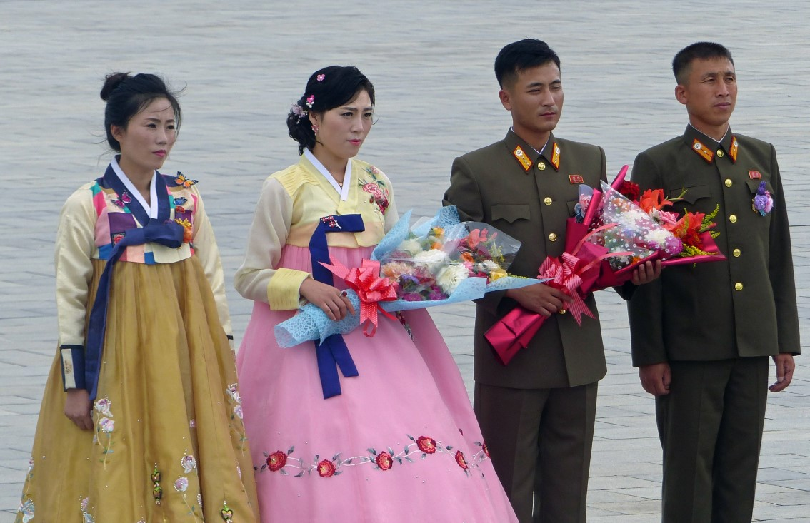 Two women in traditional dress and two men in uniform