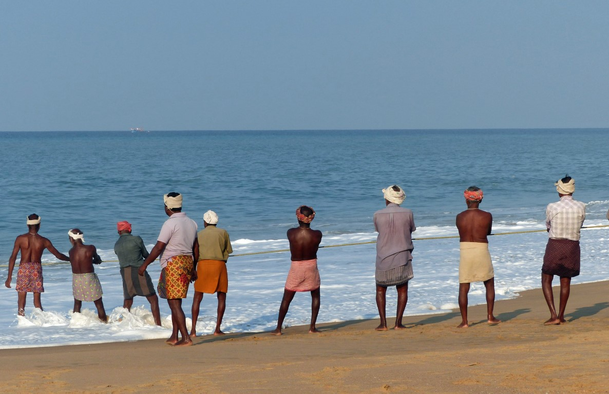 Men in turbans pulling a rope up a beach
