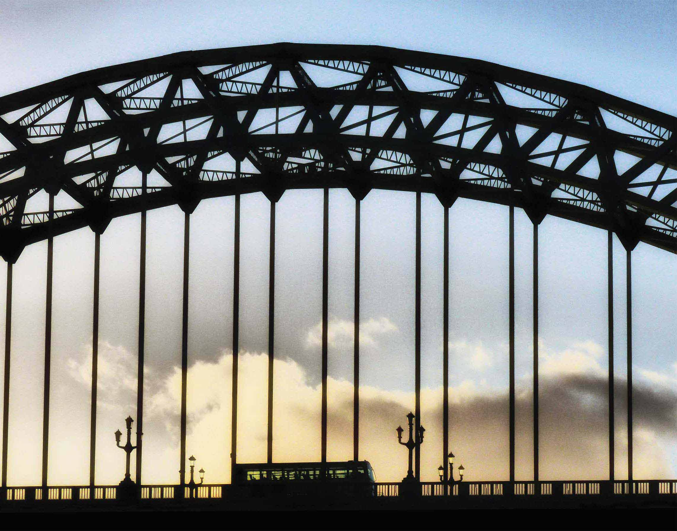 Arched bridge and bus silhouetted against sunset sky