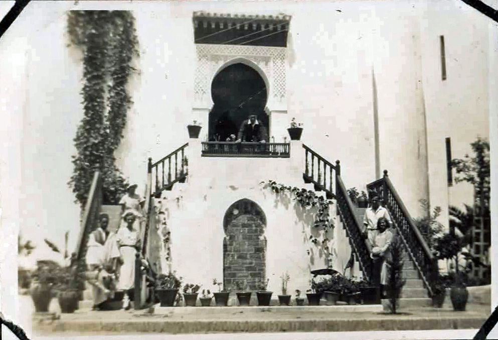 Old photo of people outside an attractive villa