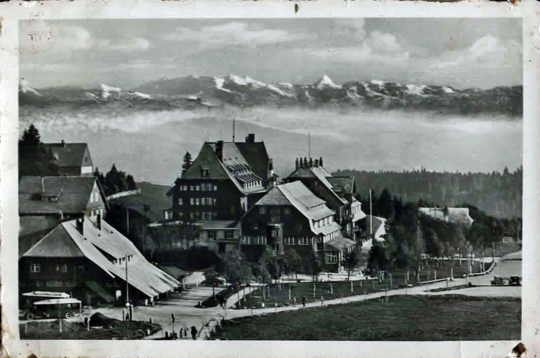 Old photo of large alpine hotel with mountains behind