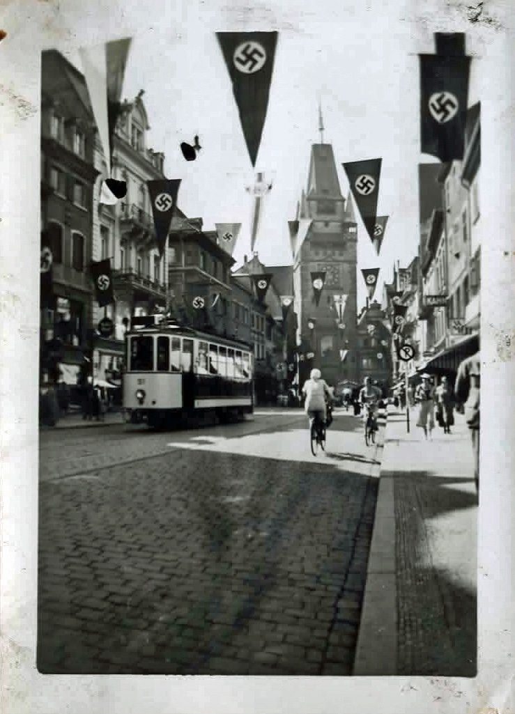 Old photo of a city street with swastika flags