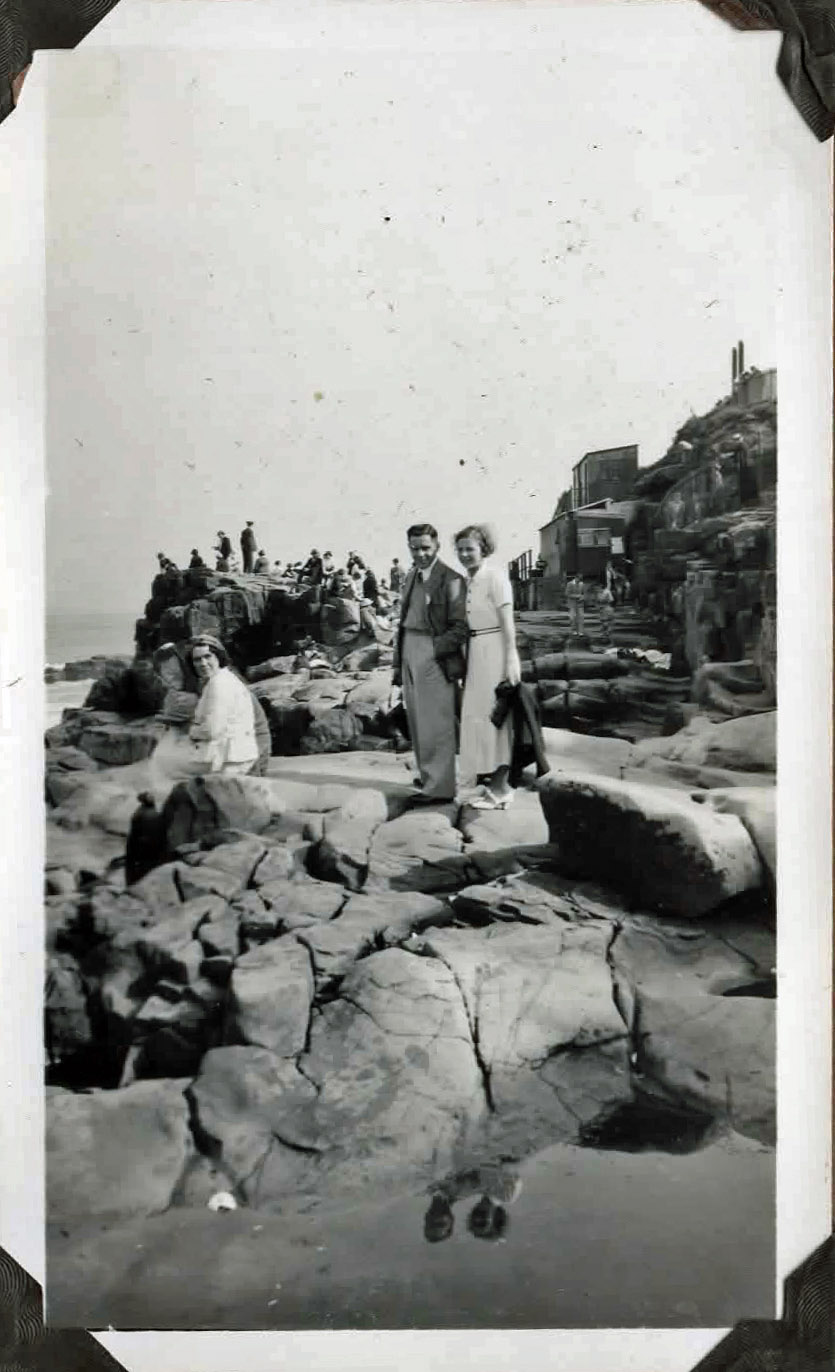 Old photo of people on rocks by the sea