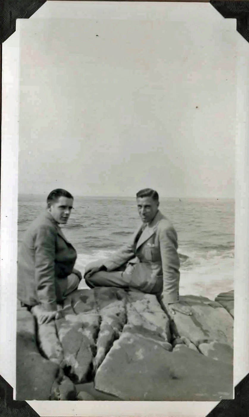 Old photo of two men sitting on rocks by the sea