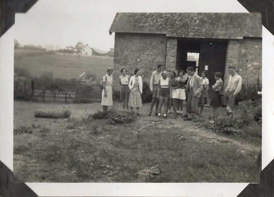 Old photo of group of people in front of a barn
