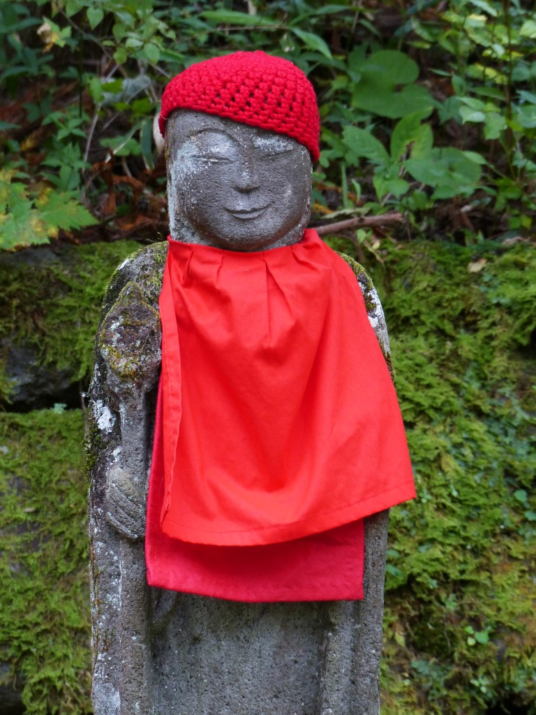 A stone statue wearing a red cap and bib