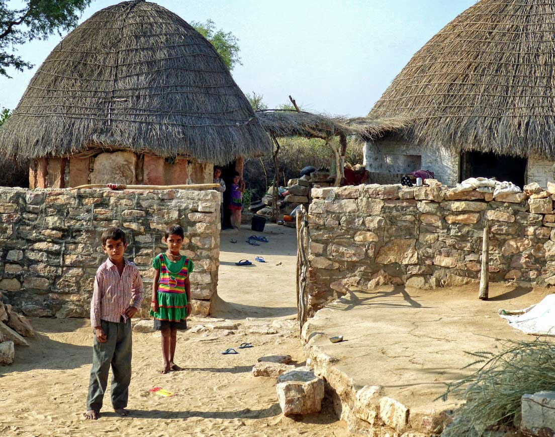 Boy and girl outside walled compound with small huts