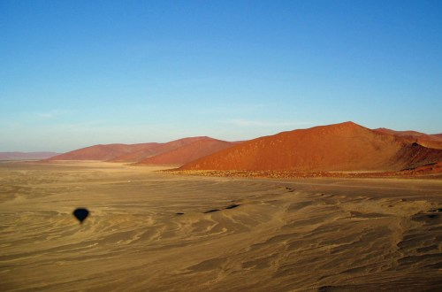 Sand dunes with shadow of a hot air balloon