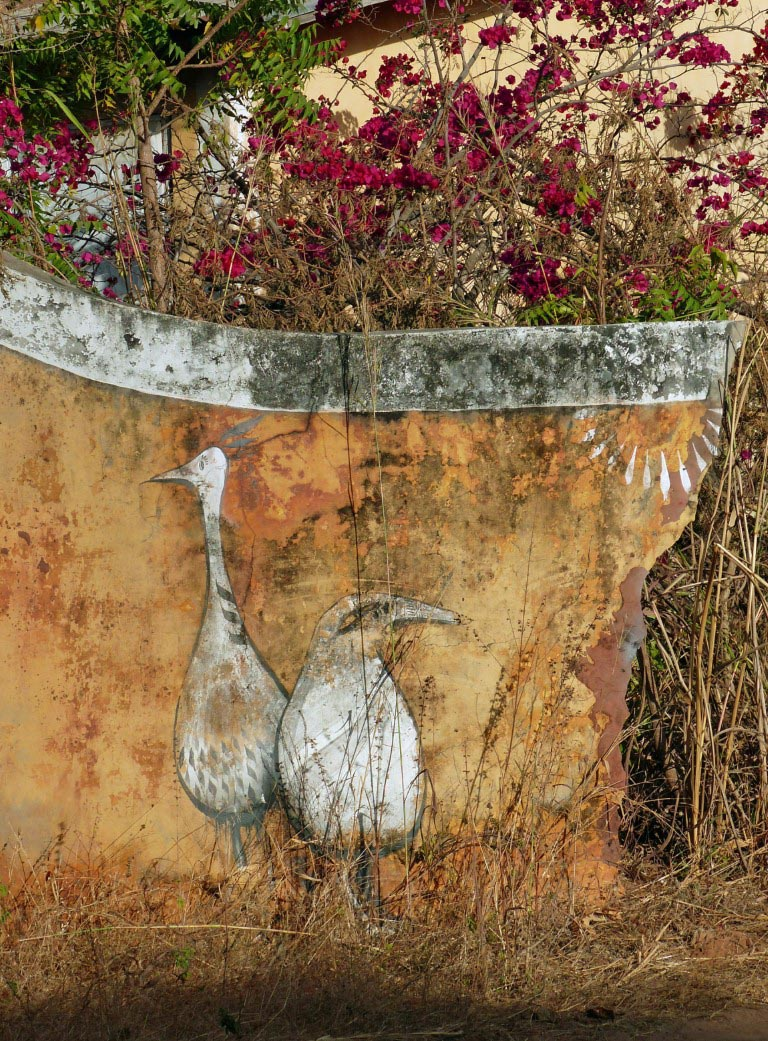 Painting of two white birds on a broken wall