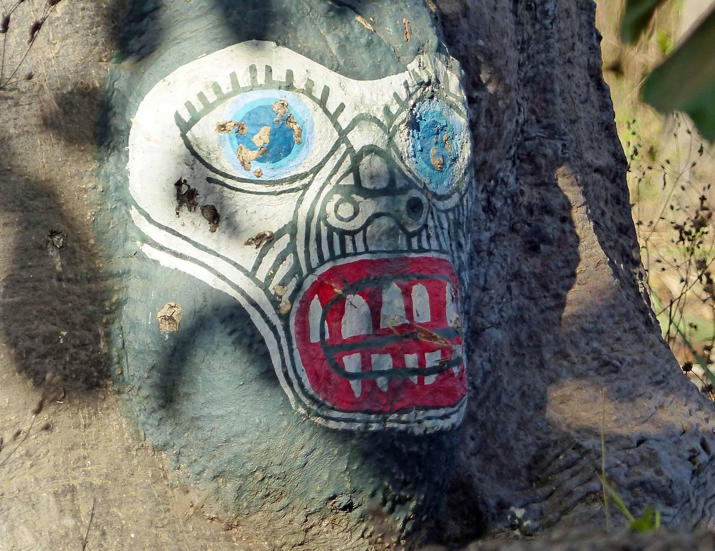 Fierce face painted on tree trunk