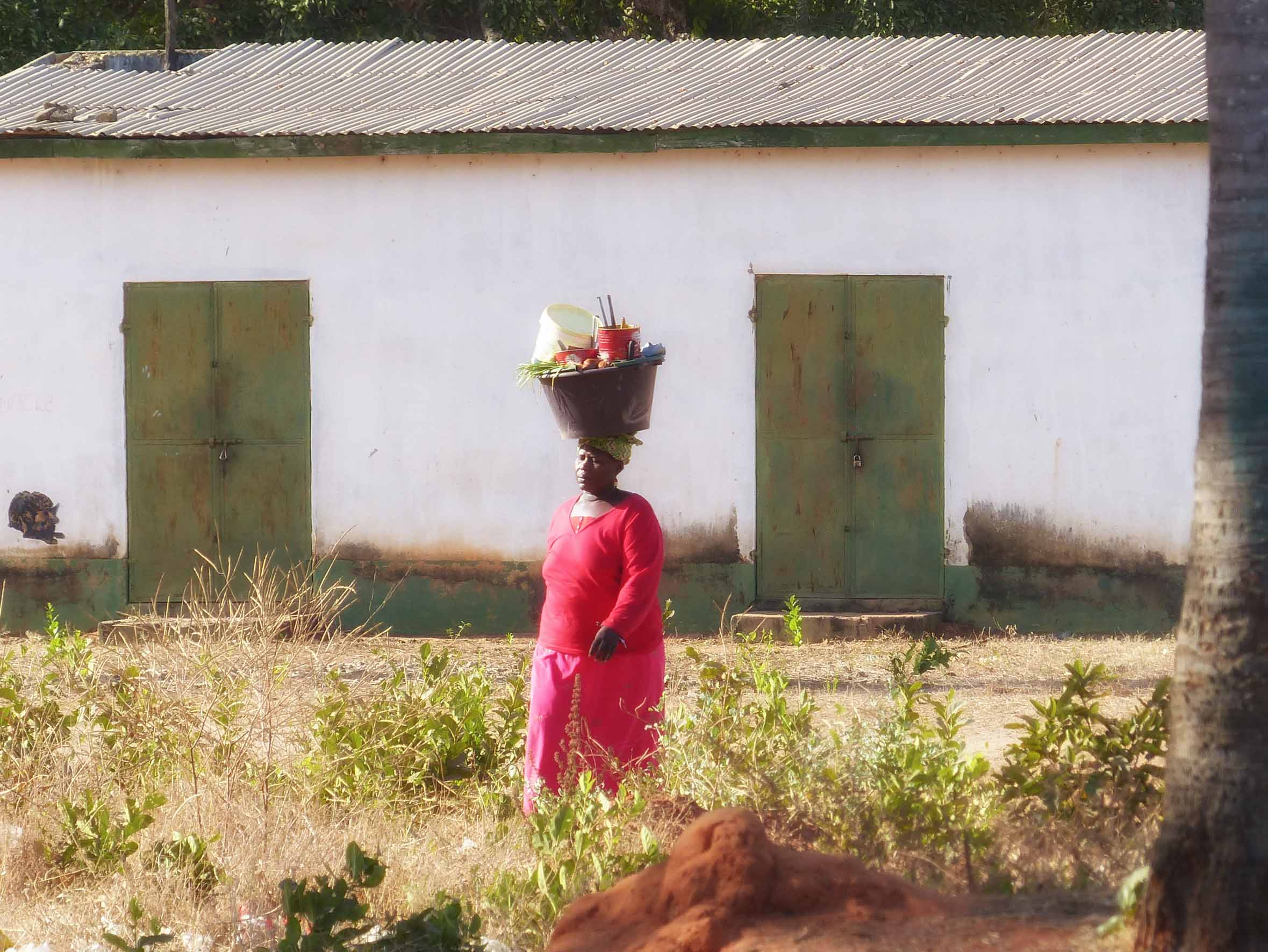 Woman in red dress carrying basket on her head