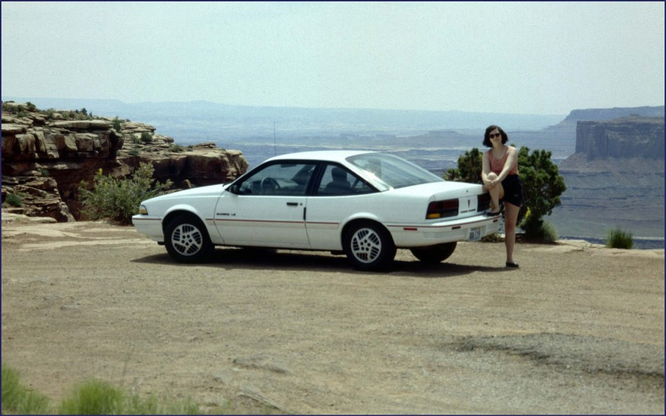 White car and woman in front of rocky landscape