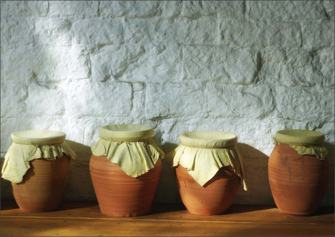 Four terracotta jars with cloth covers
