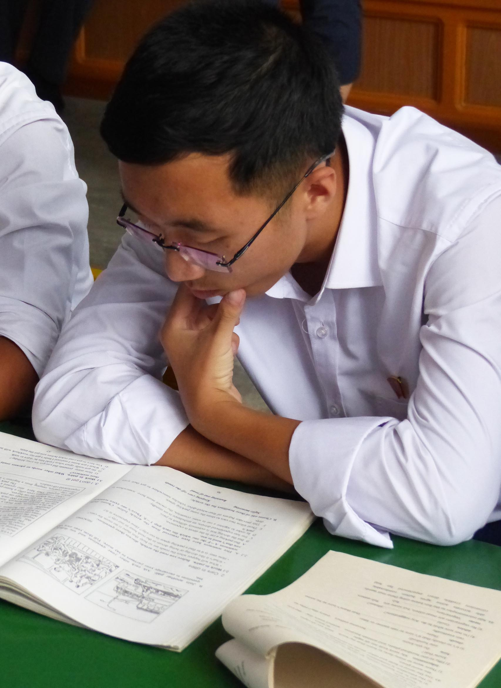 Boy in white shirt reading text book
