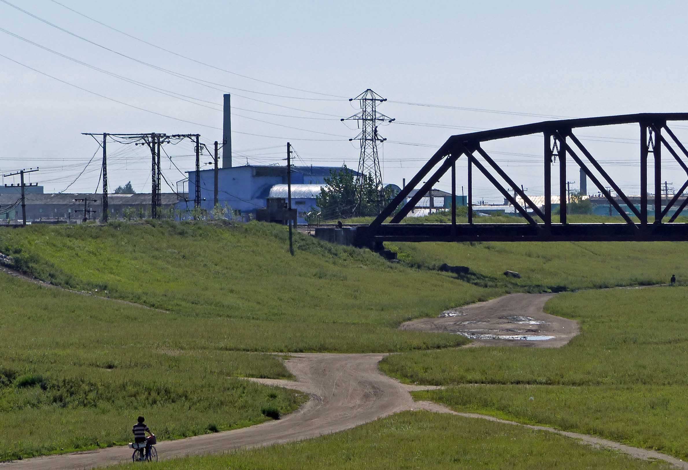 Man cycling across grassy area with factories beyond