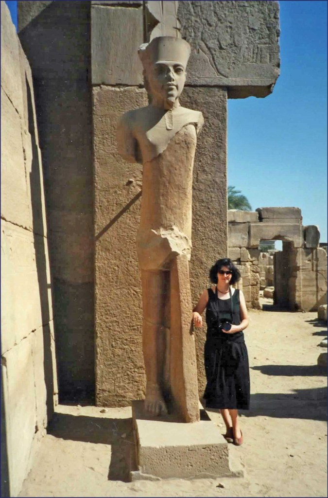 Lady in black dress by an Egyptian statue