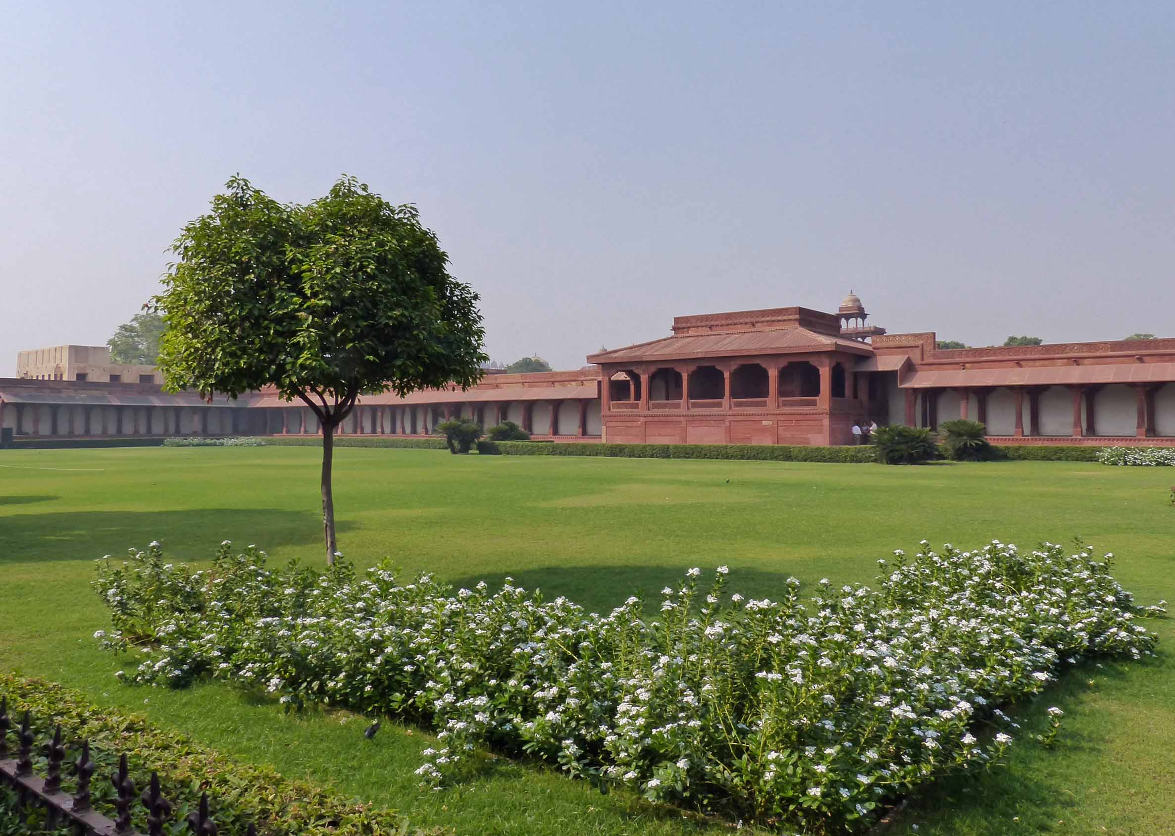 Red sandstone building on far side of large lawn