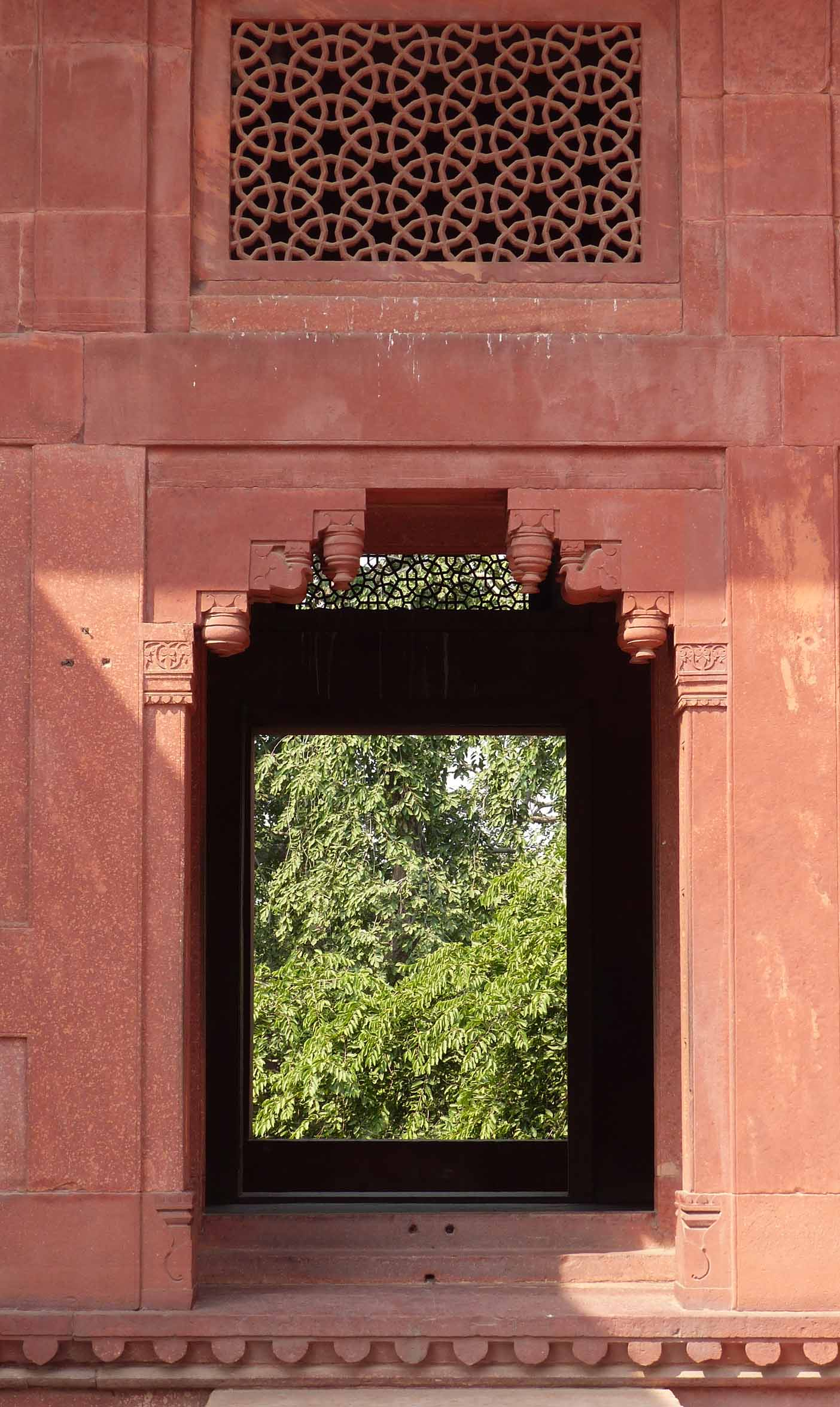 Window and carved panel in red sandstone building