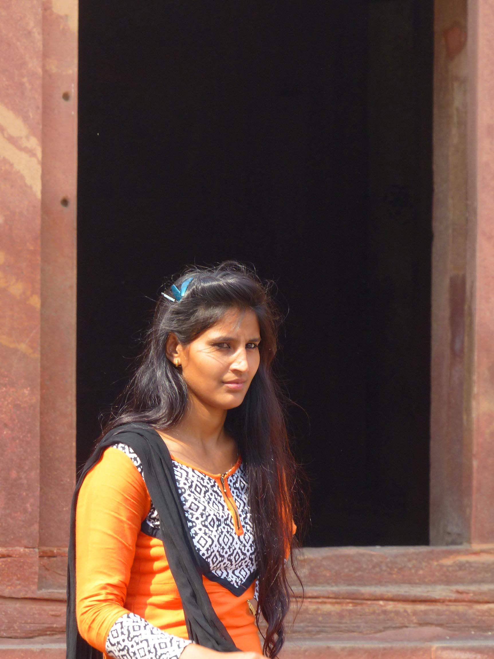 Lady in orange sari by red sandstone building