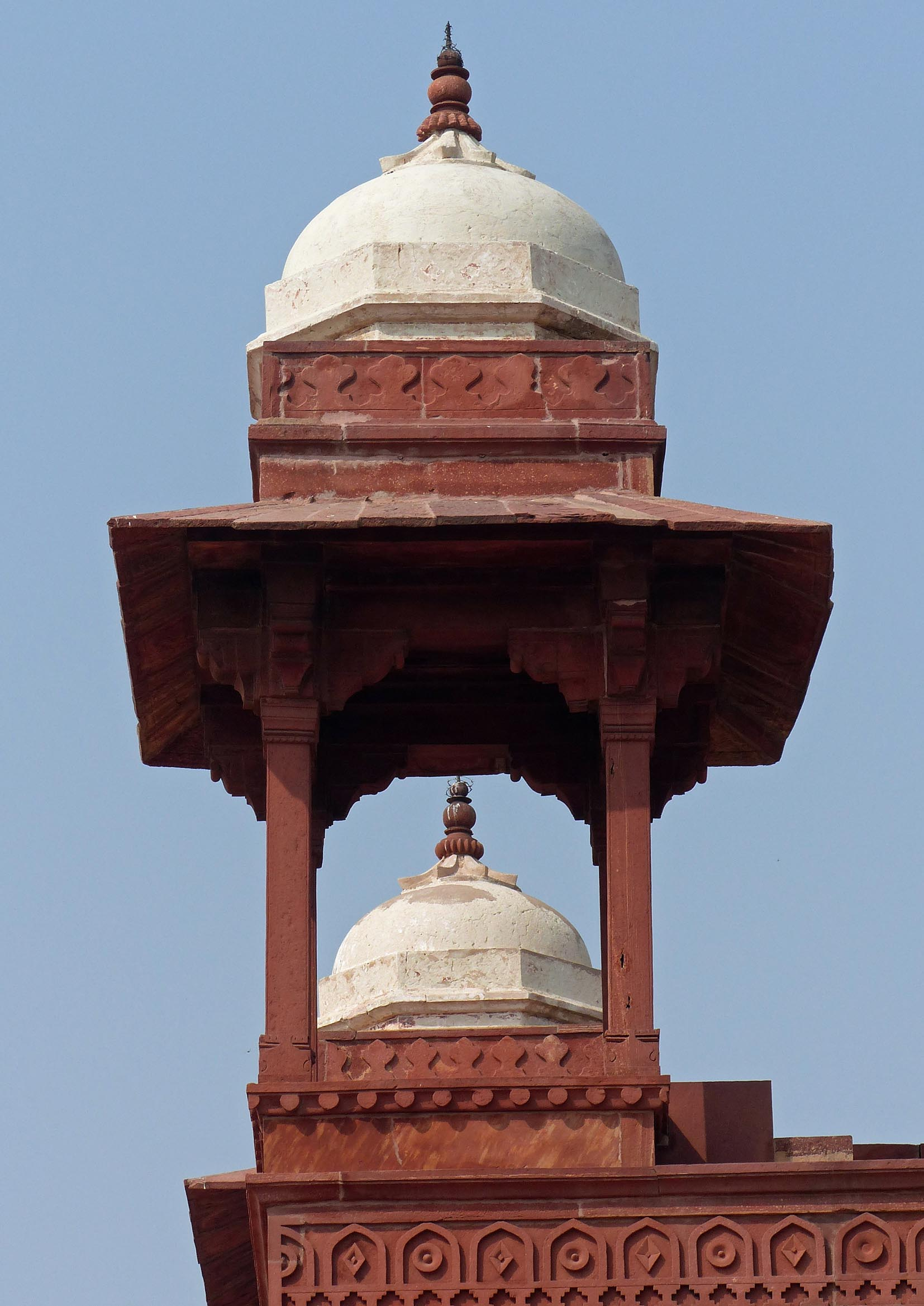 Red sandstone building with white roofed towers