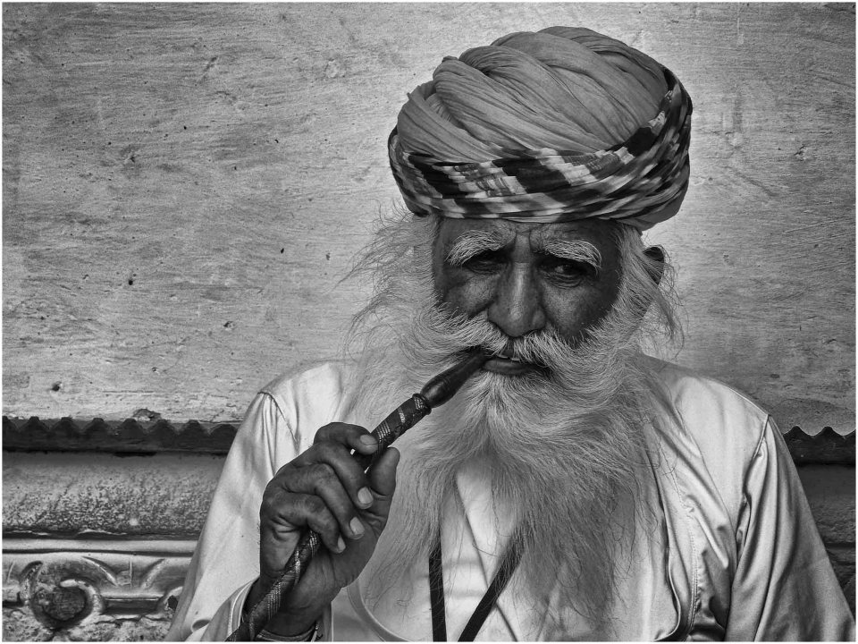 Black and white photo of a man in a turban smoking