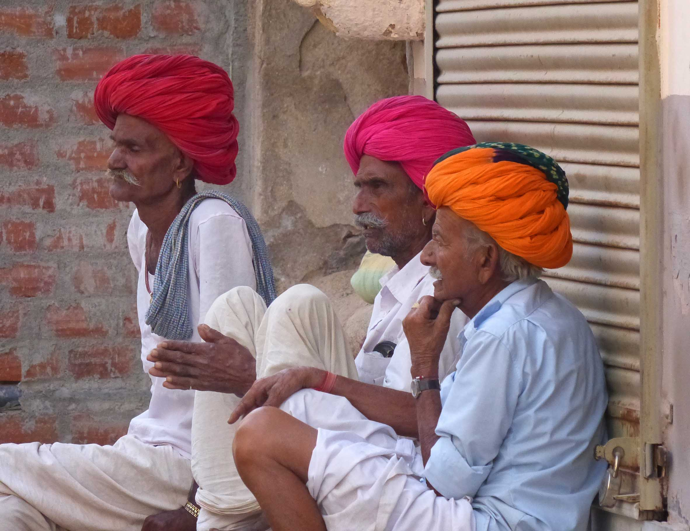 Three men in white with colourful turbans