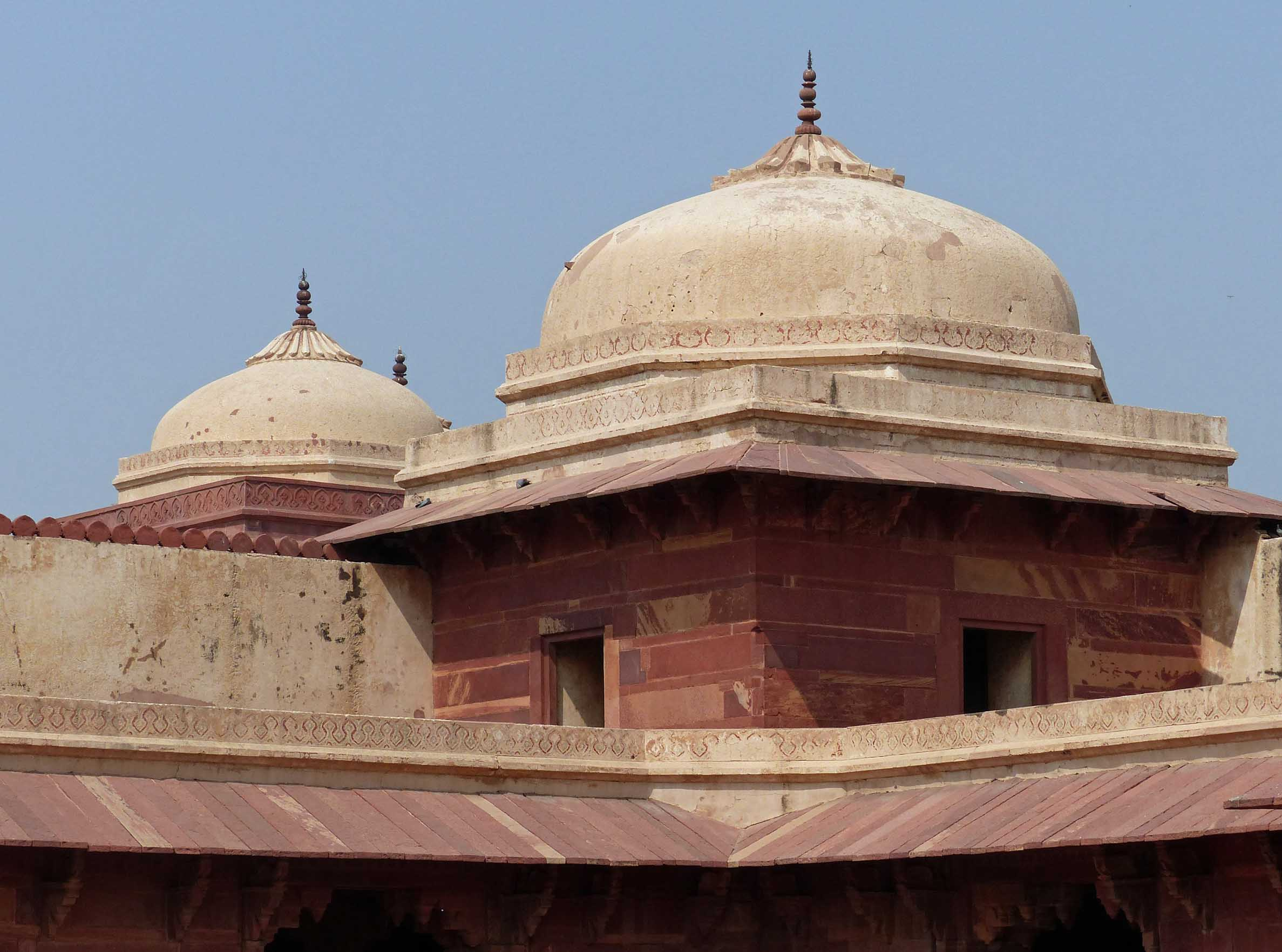 Red sandstone building with cream domes
