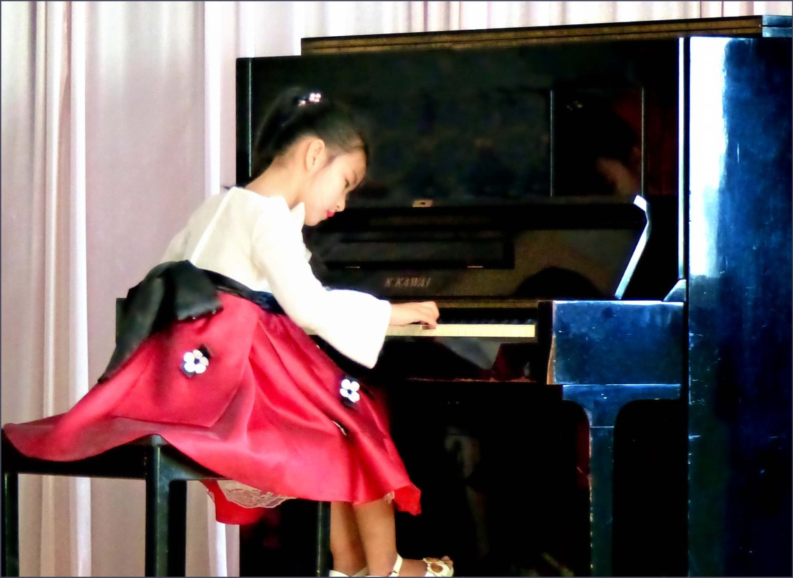 Little girl in red skirt playing piano