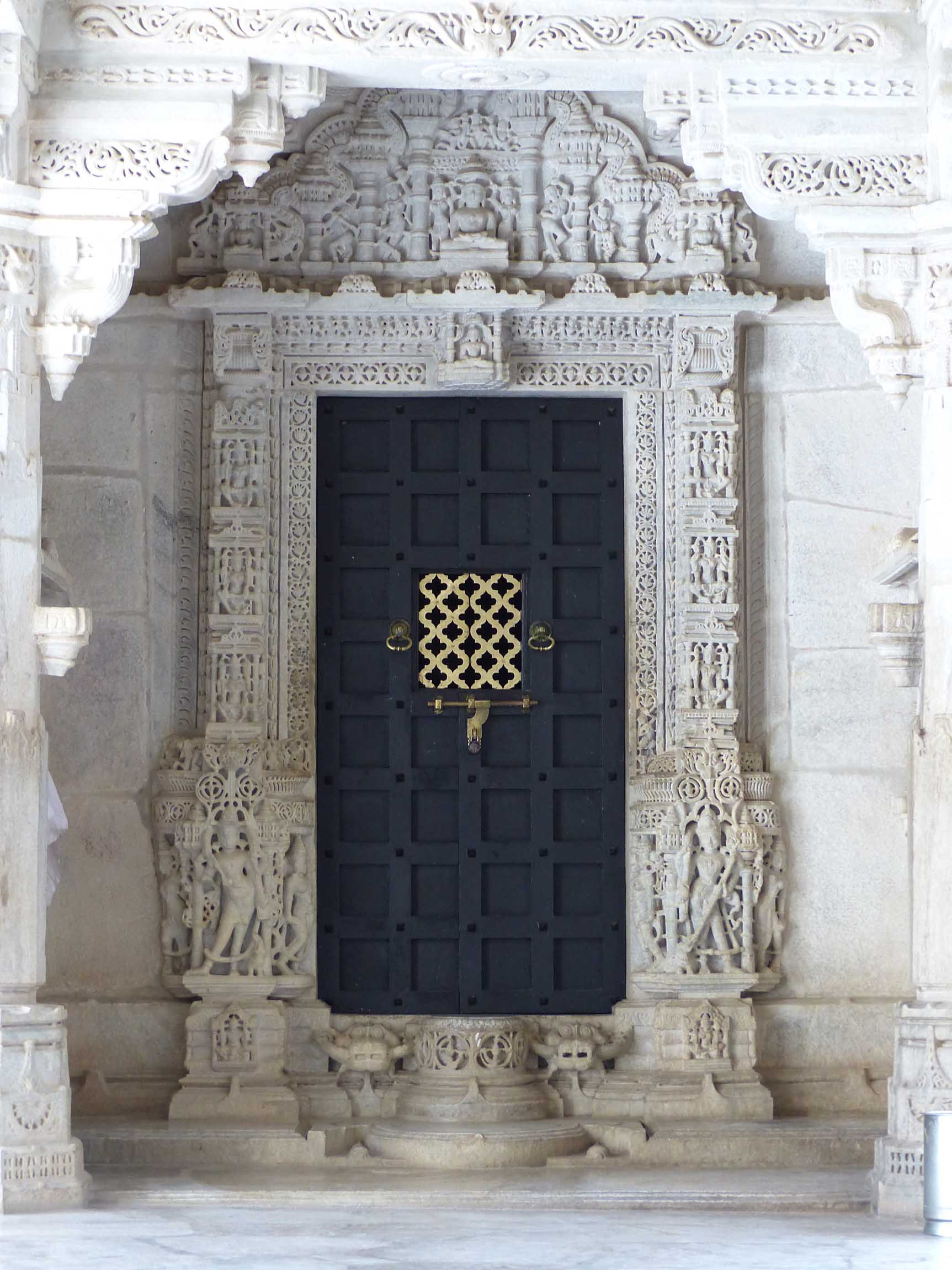Black door surrounded by carved marble walls