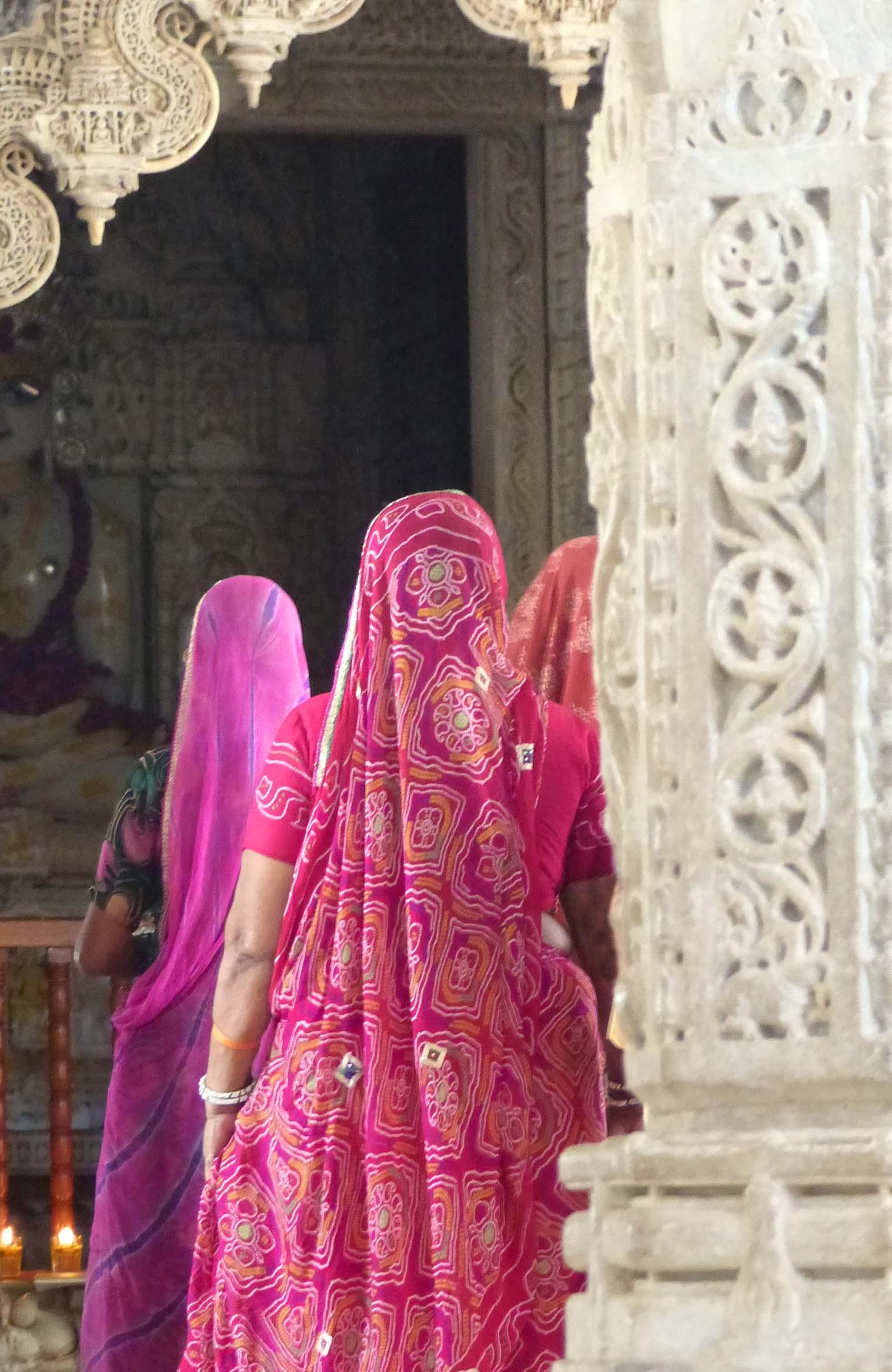 Ladies in pink saris among carved pillars