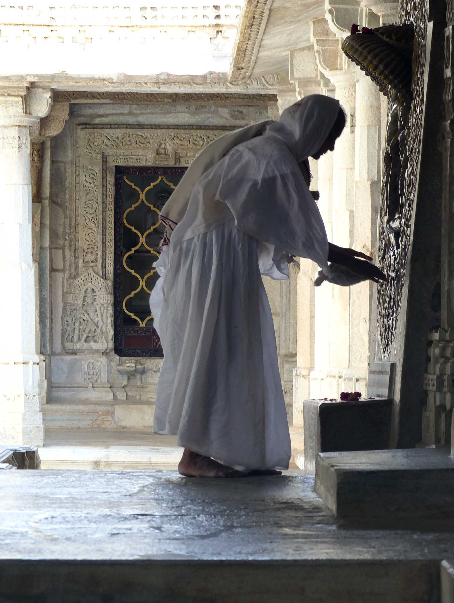Nun in white robes before a carving