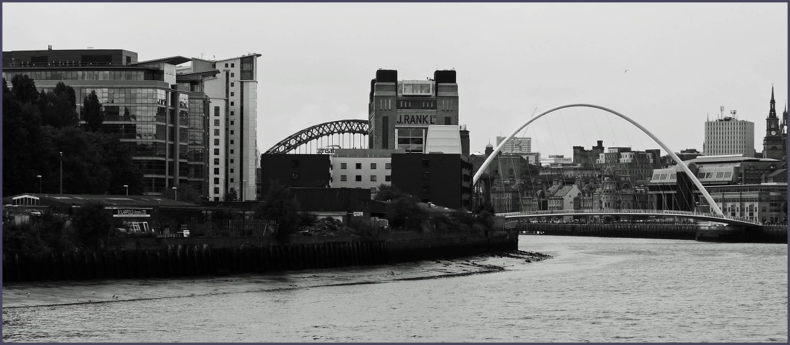 Black and white photo of a river with bridges and city buildings
