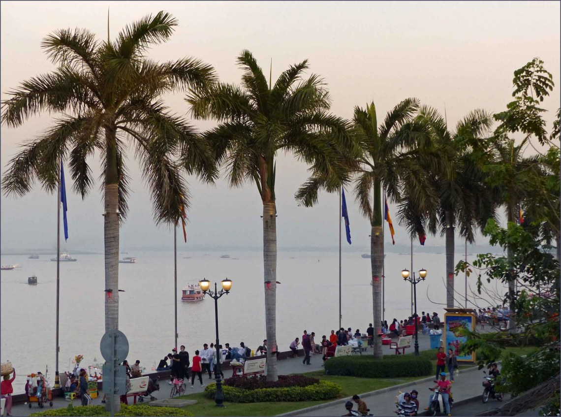 People walking by wide river lined with palm trees