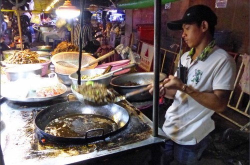 Man frying insects at a food stall