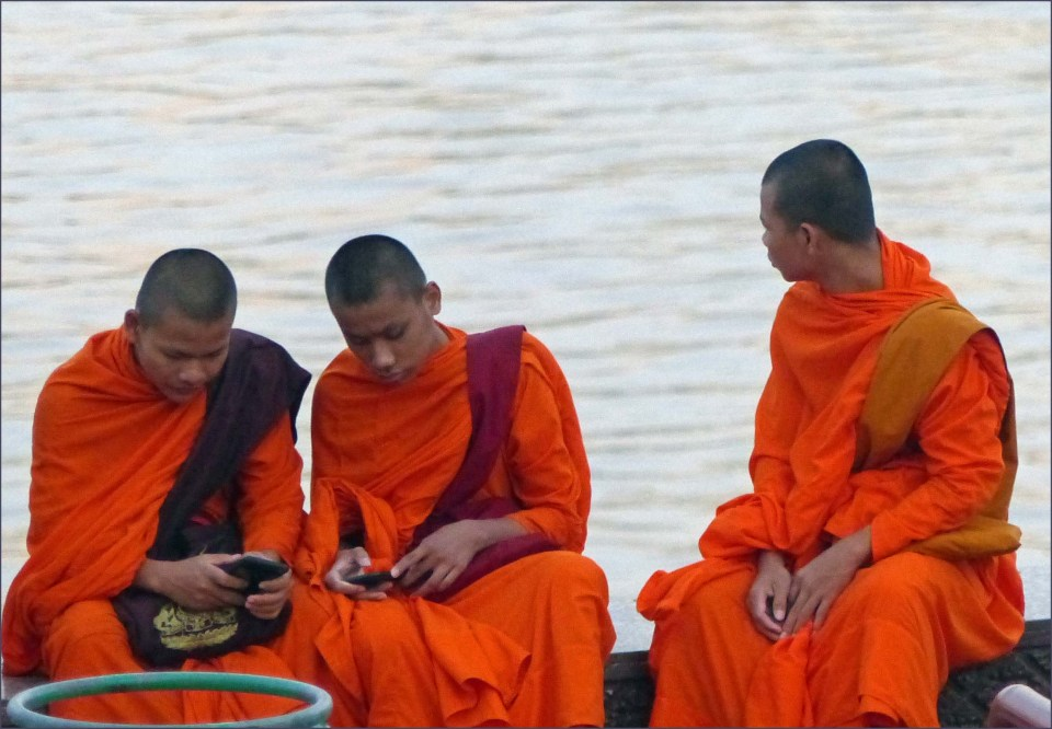 Three Buddhist monks in bright orange by a river