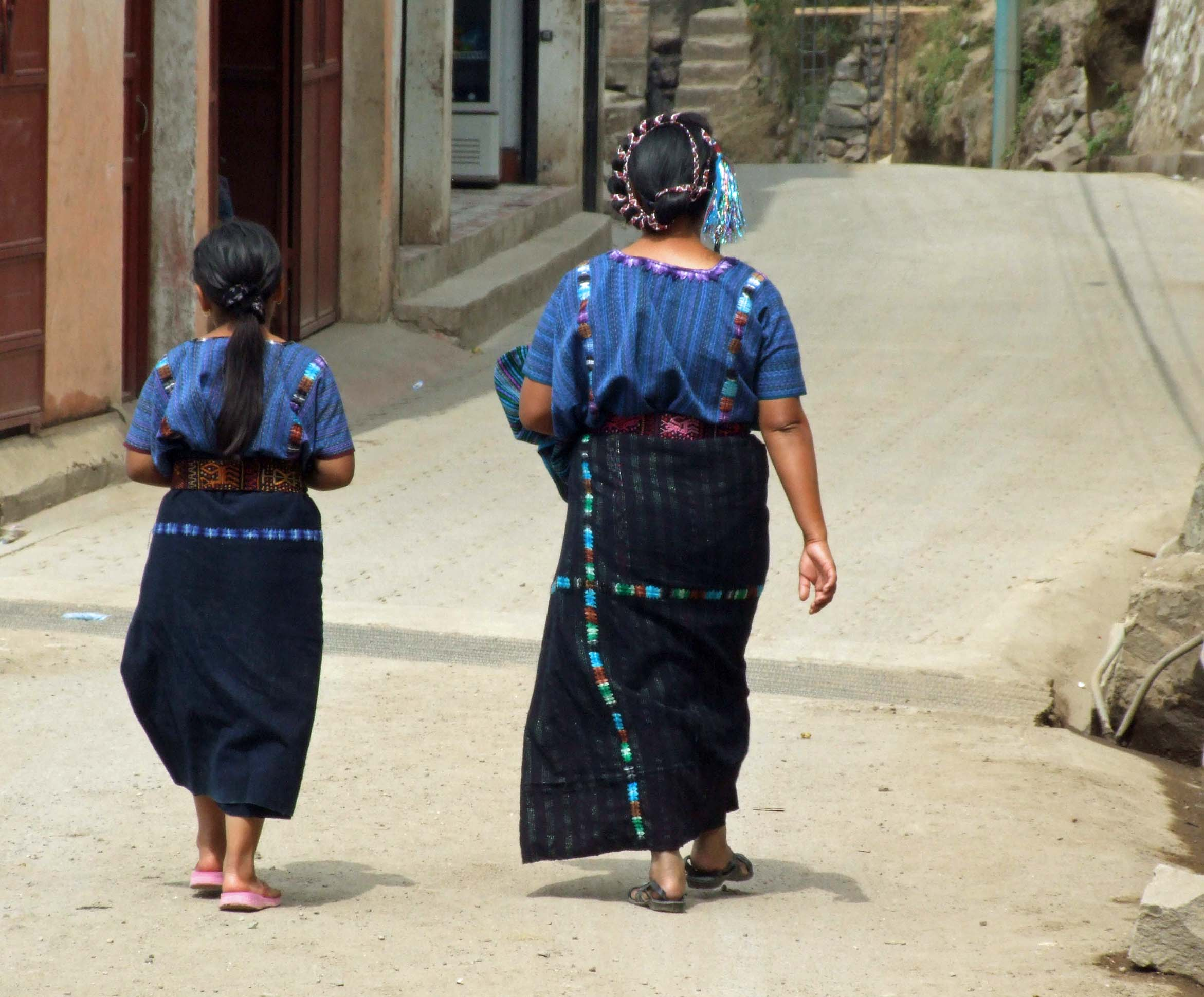 Two women in traditional blue clothing walking along a street