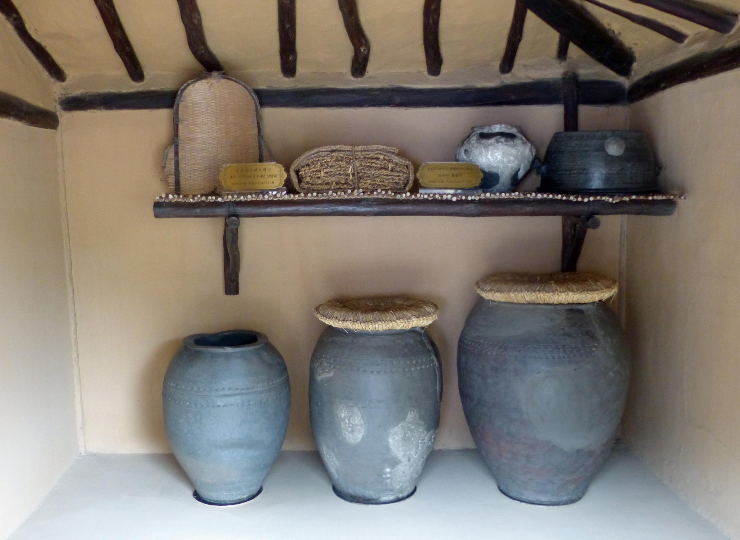 Large pots on the floor with shelf above