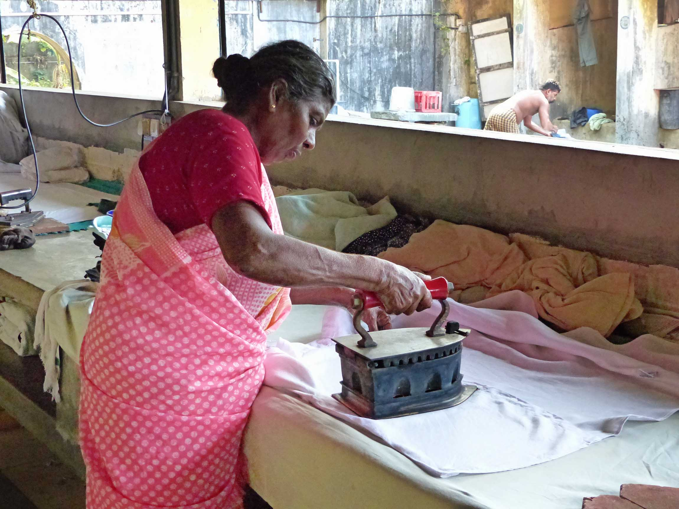 Woman in pink sari ironing