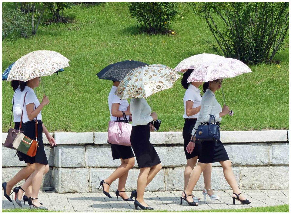 Young women in smart clothing with parasols
