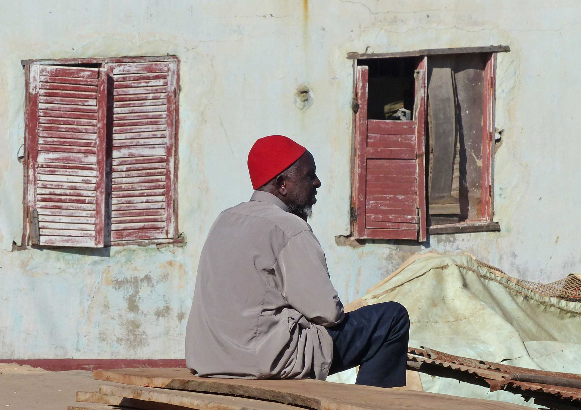 Man sitting among boats near a house