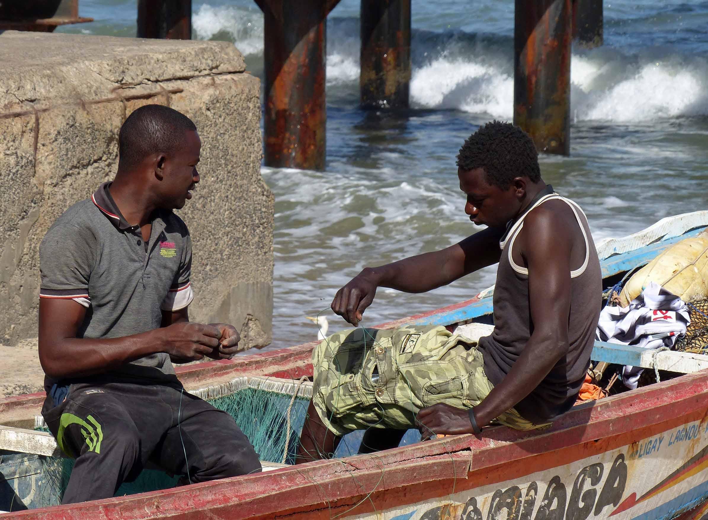 Two men in a boat mending nets