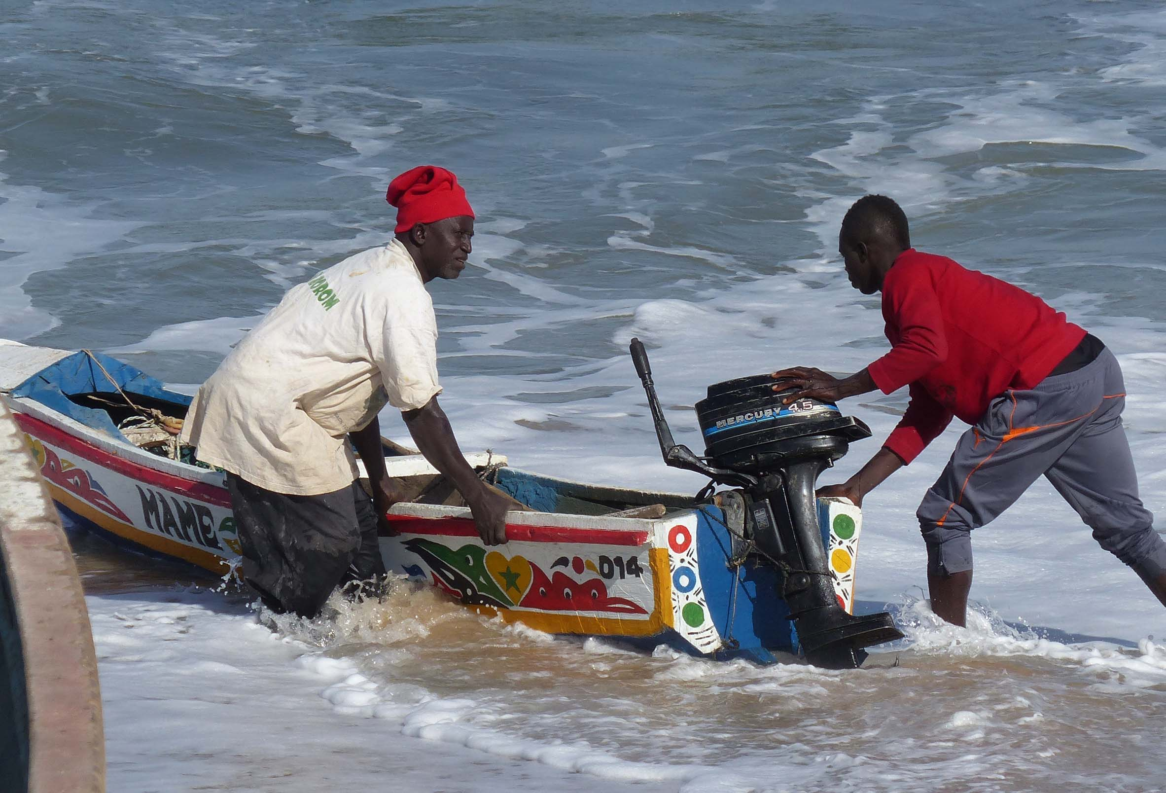 Two men dragging a small boat through the water