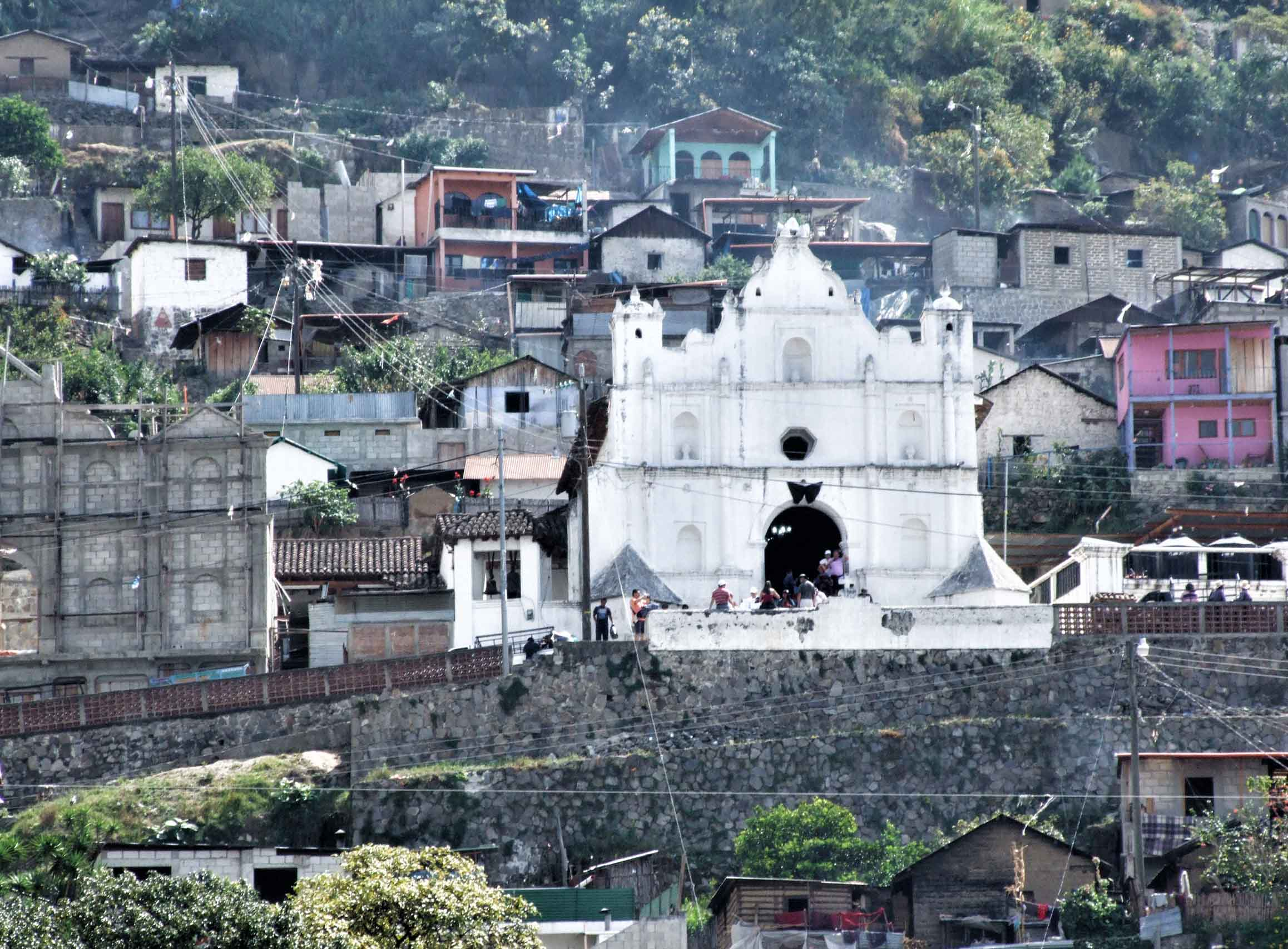 White church on a hillside surrounded by simple houses
