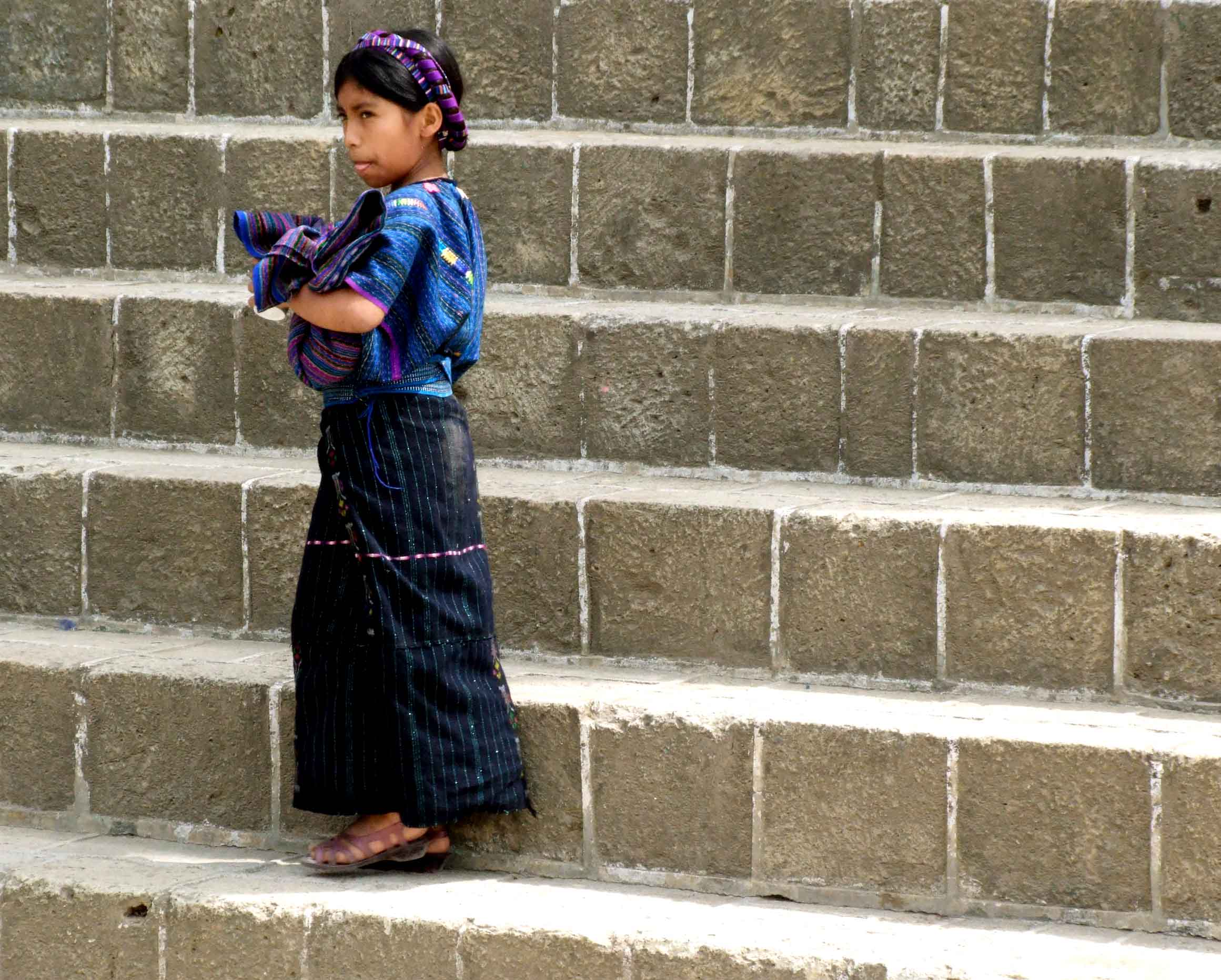 Girl in traditional blue clothing on stone steps