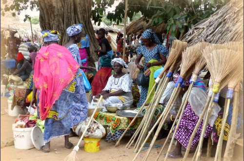 Group of women in African dress selling brooms
