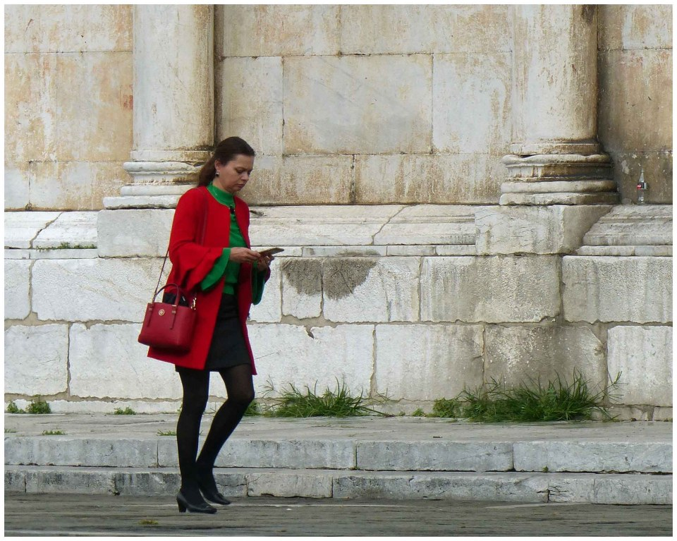 Woman in red coat passing a church
