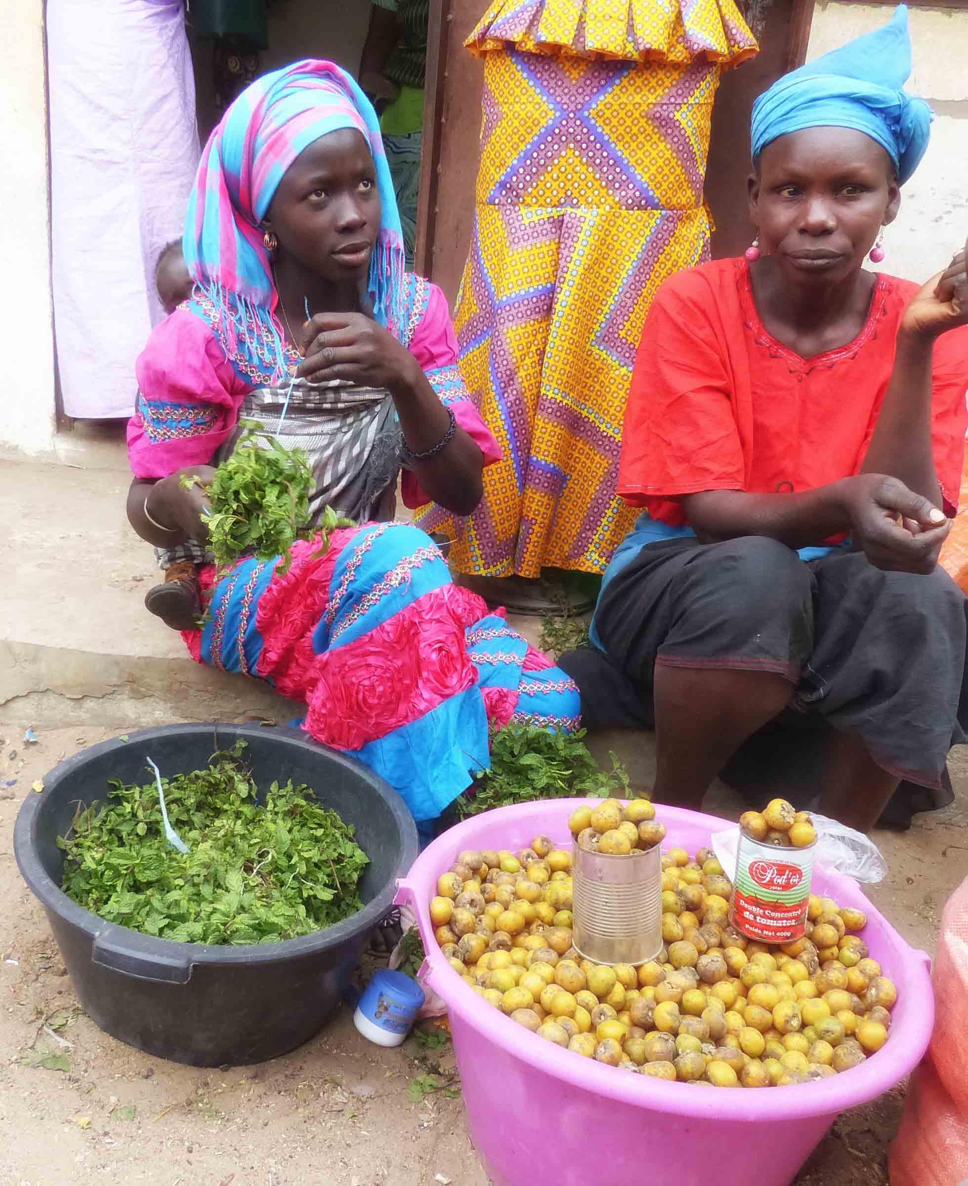 Two ladies in African dress selling vegetables