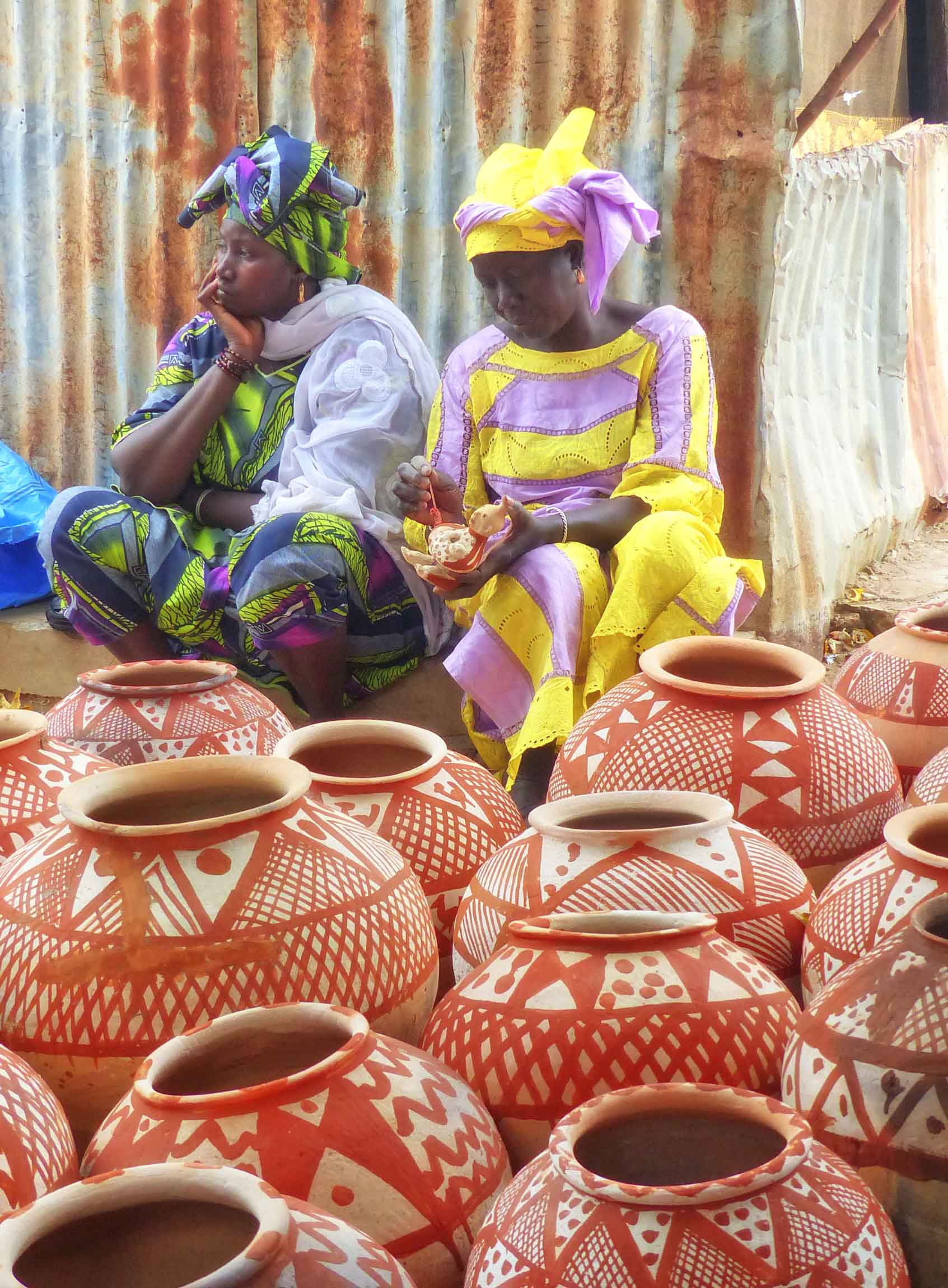 Two women in African dress selling pottery