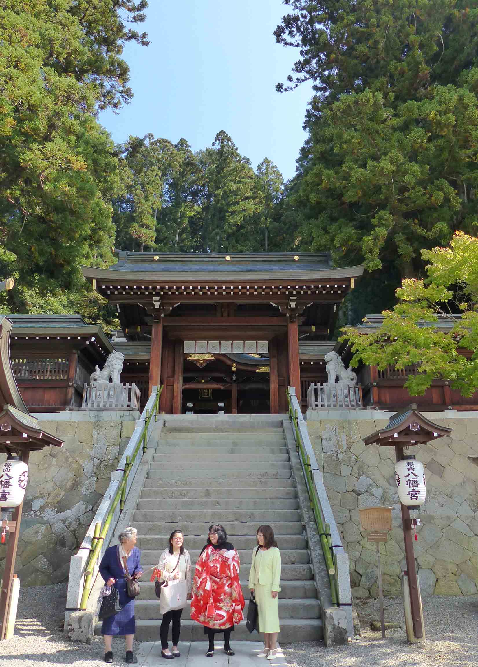 Four women in front of a shrine
