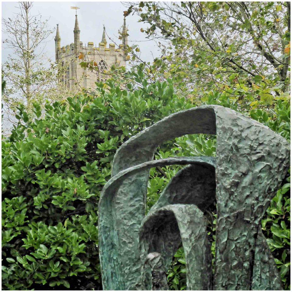 Modern sculpture in a garden with a church tower